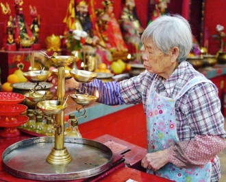 Old wrinkled chinese lady lighting incense sticks at the Tin Hau temple in Stanley.