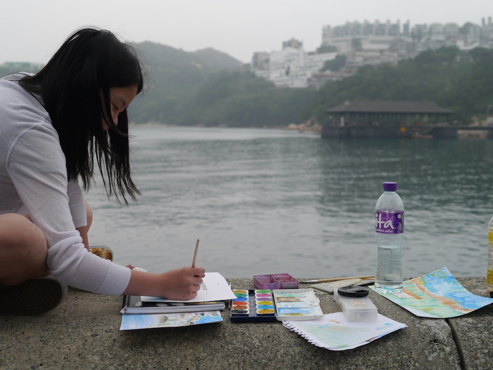 Girl painting the harbour at Stanley