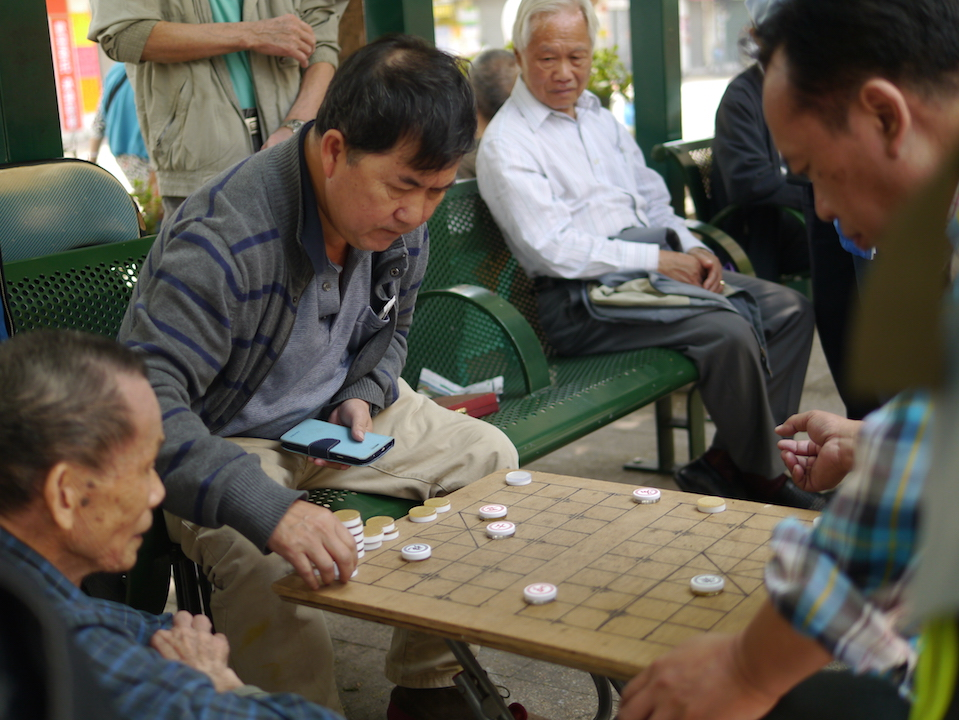 People on the street playing chinese checkers