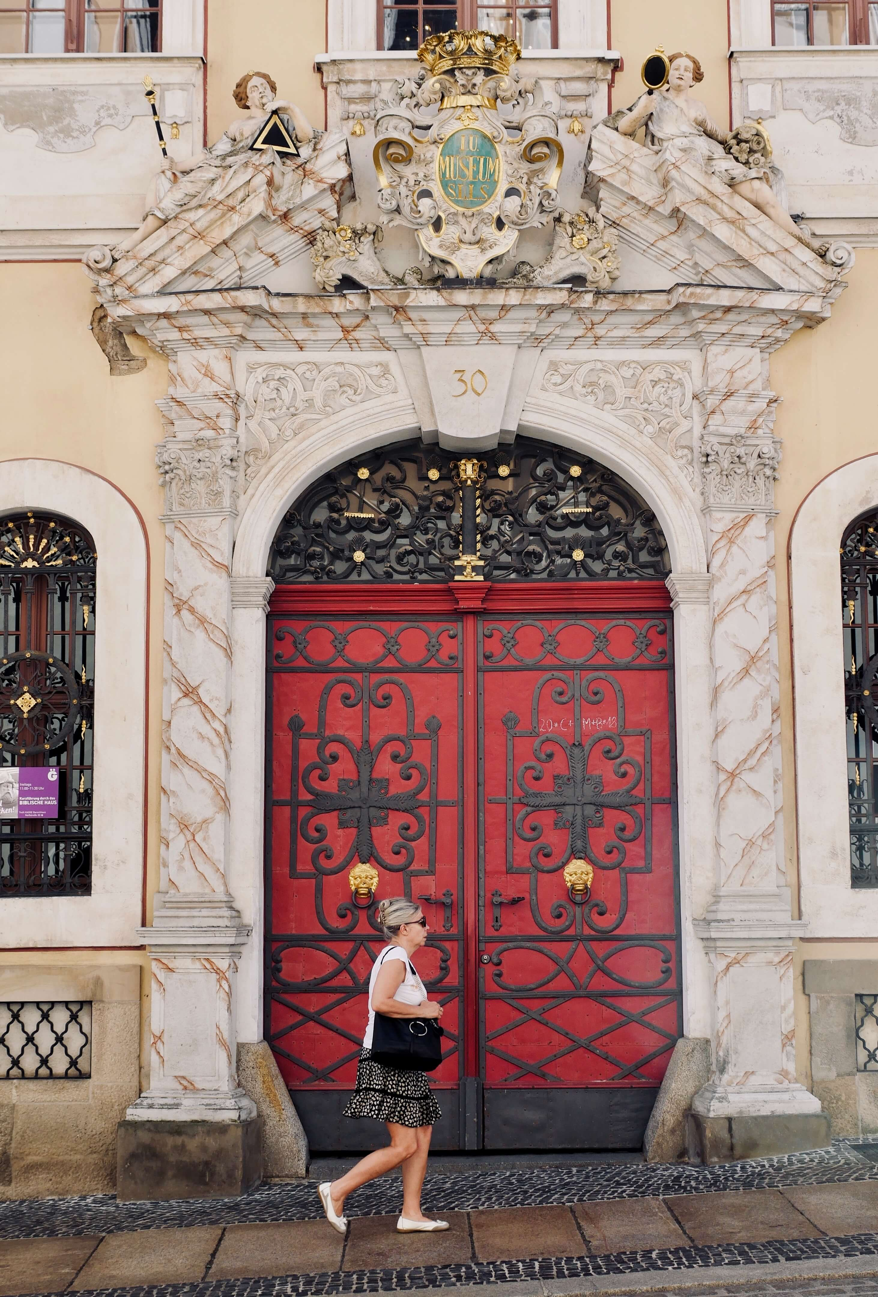 intricately carved beautiful red door with glorious marble frame